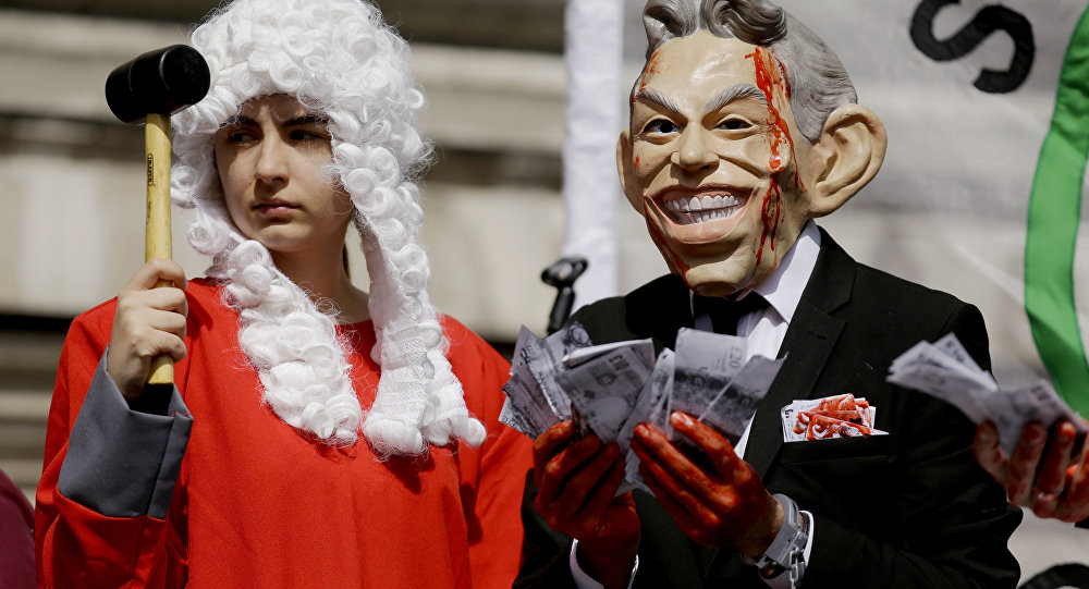 A protester wearing a former British Prime Minister Tony Blair mask, right, and another dressed as a judge pose for the media on a stage outside the Queen Elizabeth II Conference Centre in London, shortly before the publication of the Chilcot report into the Iraq war, Wednesday, July 6, 2016.