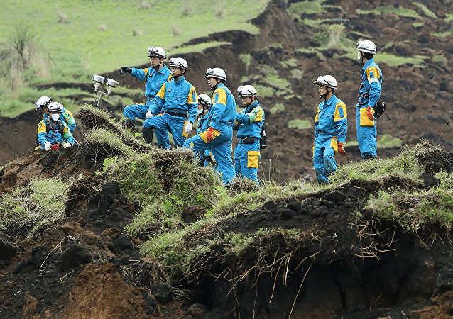 Policemen ckeck a landslide site before searching for missing people in Minami-Aso, Kumamoto prefecture, on April 22, 2016