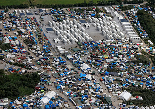 Aerial view of a makeshift camp as containers (rear) are put into place to house migrants living in what is known as the Jungle, a sprawling camp in Calais, France, August 14, 2016.