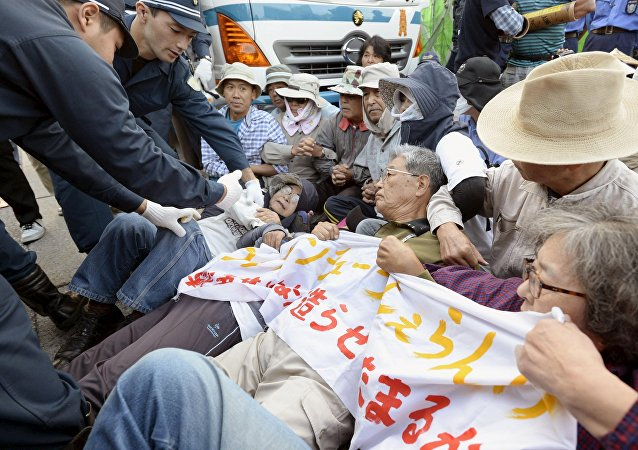Protesters lie on the ground as they try to block work on a contentious U.S. air base in front of the gate of the U.S. Marine Corps Camp Schwab in Nago on the southern Japanese island of Okinawa