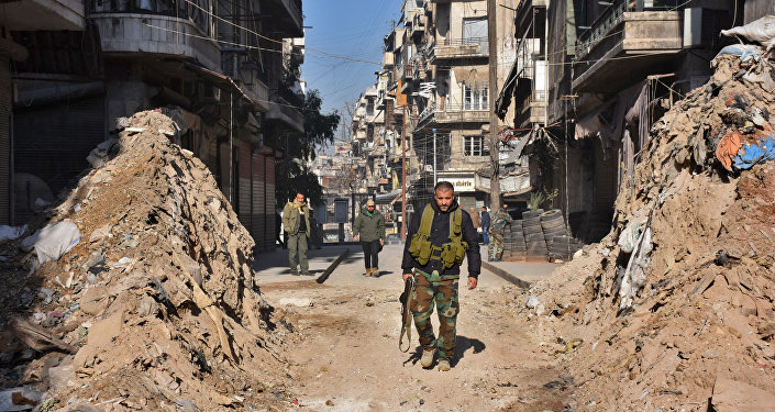 Syrian pro-government forces walk through a barricade in old Aleppo's Jdeideh neighbourhood on December 9, 2016