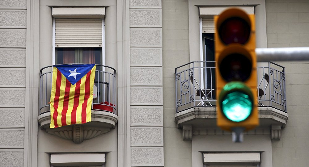 An estelada flag (Catalan separatist flag) hangs from a balcony, next to a green traffic light, in Barcelona, Spain, October 27, 2015