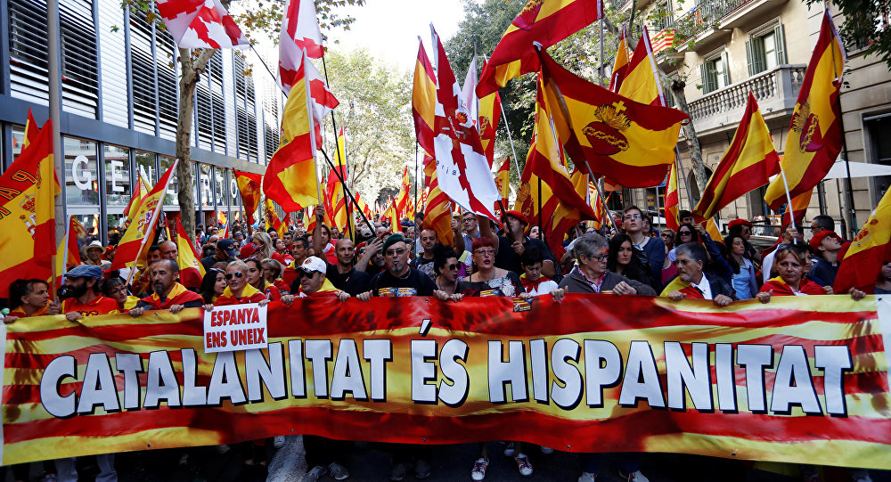 People walk behind a banner during a pro-union demonstration organised by the Catalan Civil Society organisation in Barcelona, Spain October 8, 2017