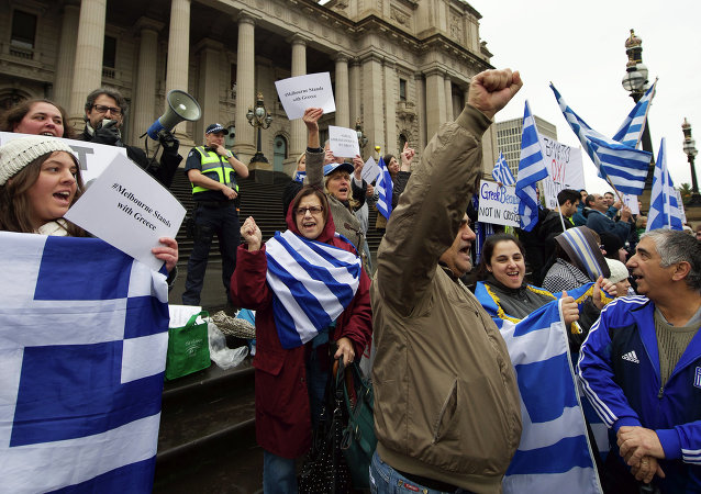 Protestors wave the Greek flag as they shout Oxi (No) during the Melbourne stands with Greece solidarity rally outside Parliament House in Melbourne on July 4, 2015