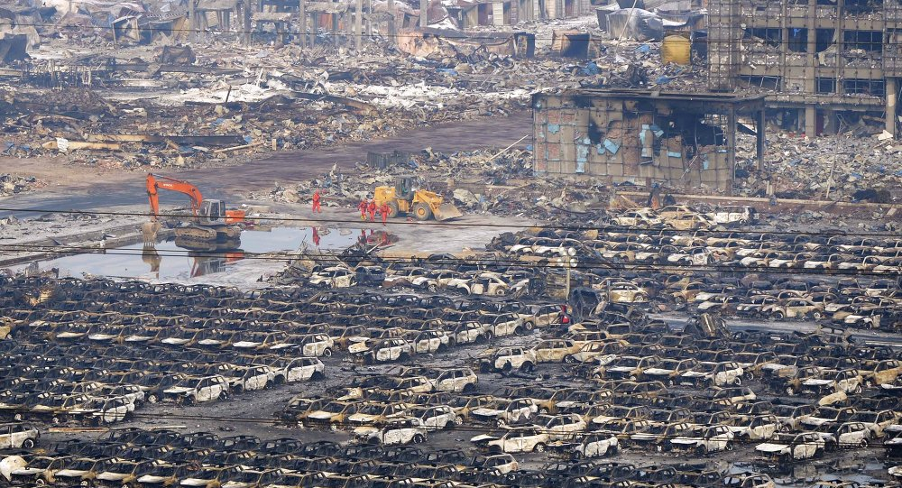 Rescuers walk next to damaged vehicles at the site of Wednesday night's explosions in Binhai new district of Tianjin, China, August 15, 2015