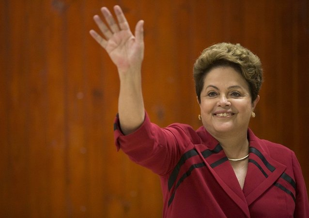 Brazil's President Dilma Rousseff, who is running for re-election with the Workers Party (PT), waves after voting in general elections in Porto Alegre, Brazil, early Sunday, Oct. 5, 2014.