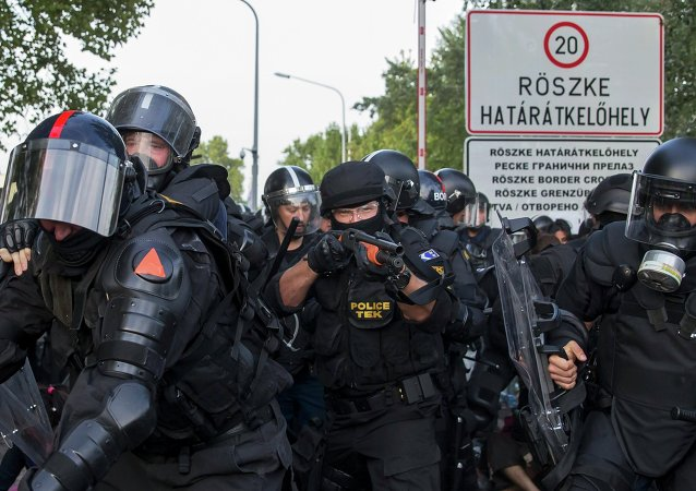 Hungarian riot police fight migrants at the border crossing with Serbia in Roszke, Hungary September 16, 2015