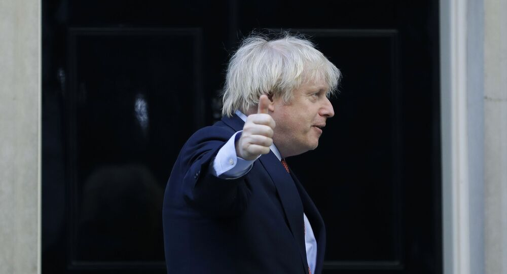 Britain's Prime Minister Boris Johnson gestures after applauding on the doorstep of 10 Downing Street, during the weekly Clap for our Carers, in London, Thursday, May 28, 2020