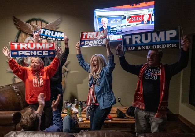 Supporters of US President Donald Trump celebrate as they watch Ohio being called for Donald Trump at a Republican watch party at Huron Vally Guns in New Hudson, Michigan, November 3, 2020