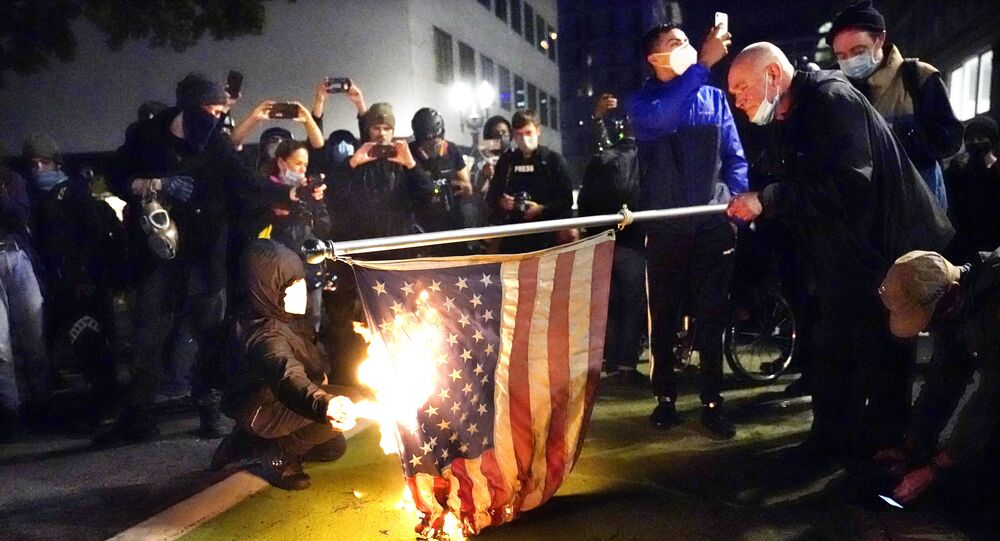 A protester lights an American flag on fire during a demonstration Wednesday, Nov. 4, 2020, in Portland, Ore