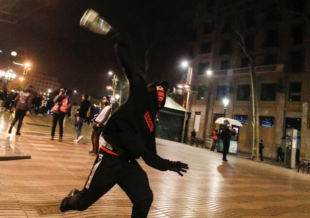 A demonstrator throws an object during a protest in support of Catalan rapper Pablo Hasel, after he was given a jail sentence on charges of glorifying terrorism and insulting royalty in his songs, in Barcelona, Spain, February 19, 2021