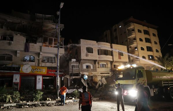 Firefighters extinguish burning apartment buildings after they were hit by Israeli airstrikes, in Gaza City, early Wednesday, May 12, 2021. (AP Photo/Adel Hana) - Sputnik Србија