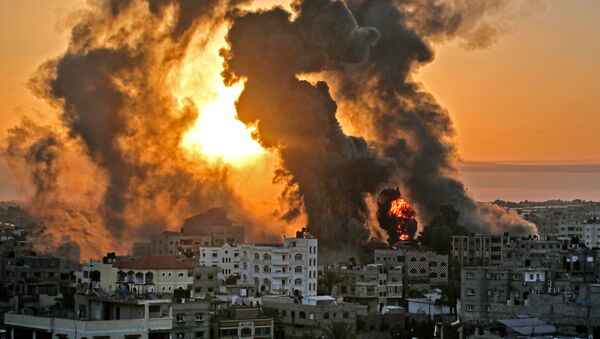 A fire rages at sunrise in Khan Yunish following an Israeli airstrike on targets in the southern Gaza strip, early on May 12, 2021. - Israeli air raids in the Gaza Strip have hit the homes of high-ranking members of the Hamas militant group, the military said Wednesday, with the territory's police headquarters also targeted. (Photo by YOUSSEF MASSOUD / AFP) - Sputnik Srbija