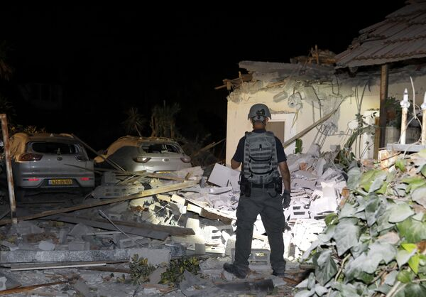 An Israeli security officer inspects damages at a house in Yehud, near Tel Aviv, on May 12, 2021, after rockets were launched towards Israel from the Gaza Strip controlled by the Palestinian militant group Hamas. - Palestinian militant group Hamas said on May 12 it had fired more than 200 rockets into Israel in retaliation for strikes on a tower block in Gaza. - Sputnik Србија