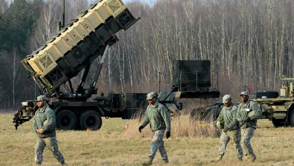 U.S soldiers walk next to a Patriot missile defence battery during join exercises at the military grouds in Sochaczew, near Warsaw - Sputnik Srbija