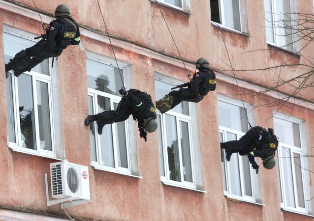 Law enforcement officers storm a building during a training session on neutralizing criminals and releasing hostages held at a comprehensive school
