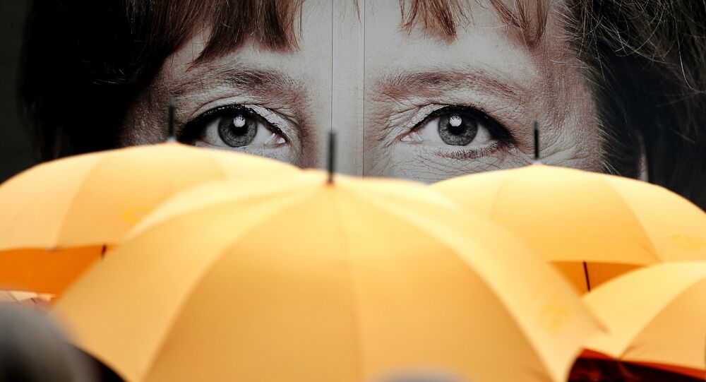 Supporters of the Christian Democratic Union (CDU) hold umbrellas in front of a giant portrait of German Chancellor Angela Merkel during an election campaign event in front of the party's headquarter in Berlin, Germany, Monday, Sept. 16, 2013.
