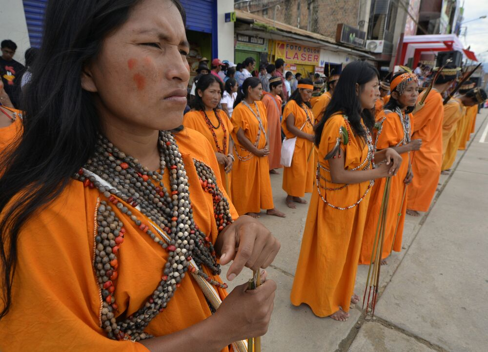 Female Amazonian natives members of military-trained self-defense committees against guerrillas and drug traffickers, stand in formation during a parade after receiving medical care, some field work stuff and shotguns on September 19, 2013, in the town of San Martin de Pagoa, 350 kilometers east from Lima in central Peru