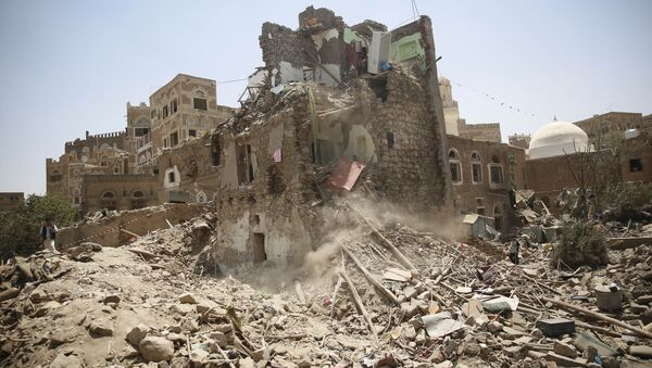 A man, left, stands guard amid the rubble of a house damaged in a Saudi-led airstrike in Sanaa, Yemen, Saturday, Sept. 19, 2015. - Sputnik Srbija