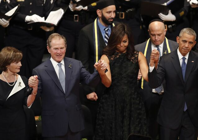 From left, former first lady Laura Bush, former President George W. Bush, first lady Michelle Obama and President Barack Obama join hands during a memorial service at the Morton H. Meyerson Symphony Center with the families of the fallen police officers, Tuesday, July 12, 2016, in Dallas