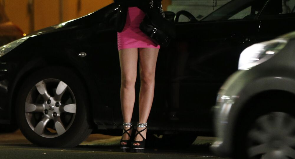 A prostitute waits for clients in a street