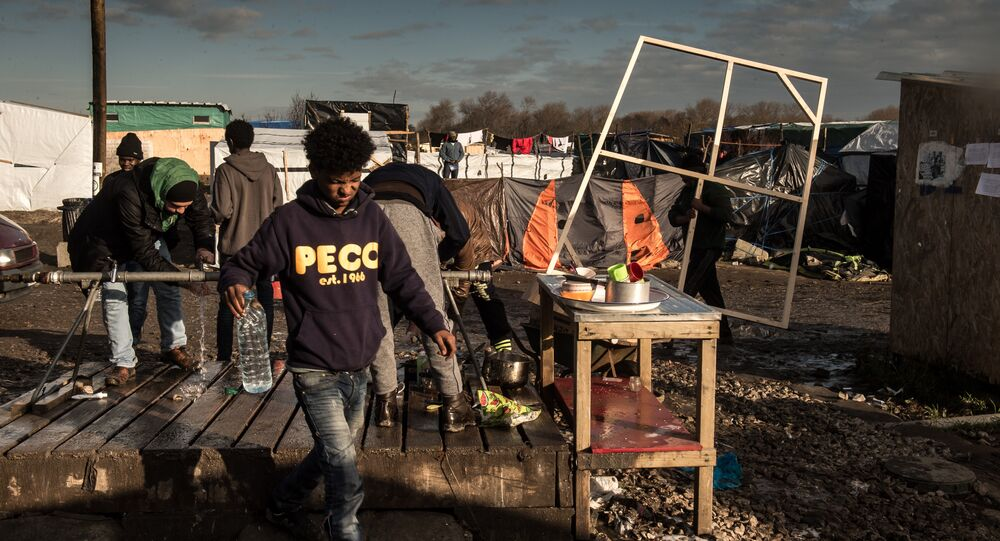 Men wash up at a water source at the migrant camp known as the Jungle in Calais on December 7, 2015