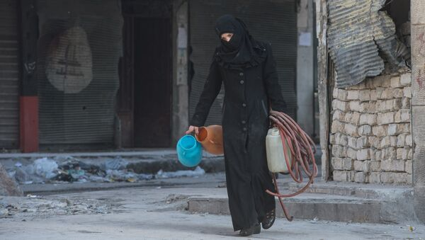 A woman walks in a residential area of Aleppo, a city divided by a front line (File) - Sputnik Srbija