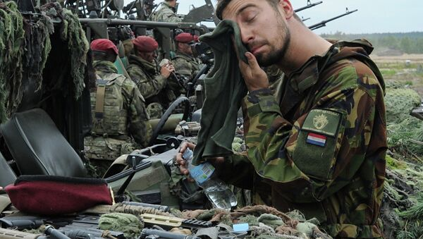 A Royal Dutch Army soldier wipes his face after the NATO Noble Jump exercise on a training range in Poland. - Sputnik Србија