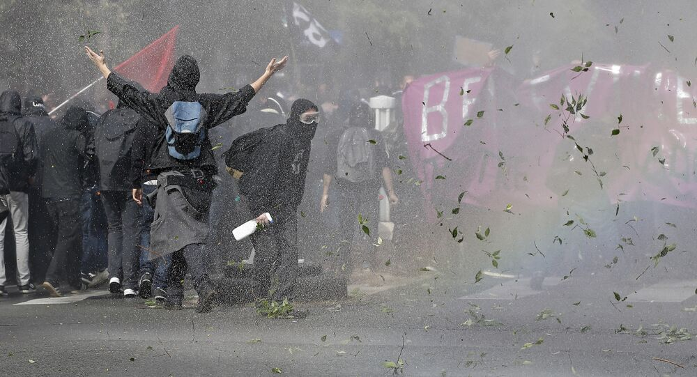 Demonstrators take cover after clashing with police during a protest march against President Emmanuel Macron's new pro-business labor policies in Paris, Tuesday, Sept. 12, 2017