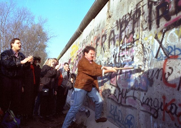 An unidentified West Berliner swings a sledgehammer, trying to destroy the Berlin Wall near Potsdamer Platz, on November 12, 1989, where a new passage was opened nearby