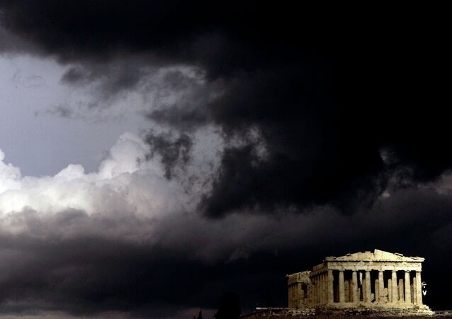 Dark clouds pass over a semi-sunlit Parthenon temple atop the ancient Acropolis Hill in Athens