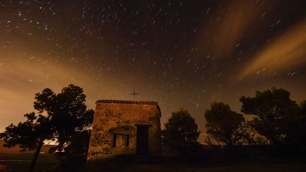 Stars seen as streaks from a long camera exposure are seen behind Arnotegui Hermitage, in Obanos, northern Spain, Tuesday, Aug. 11, 2015 - Sputnik Srbija