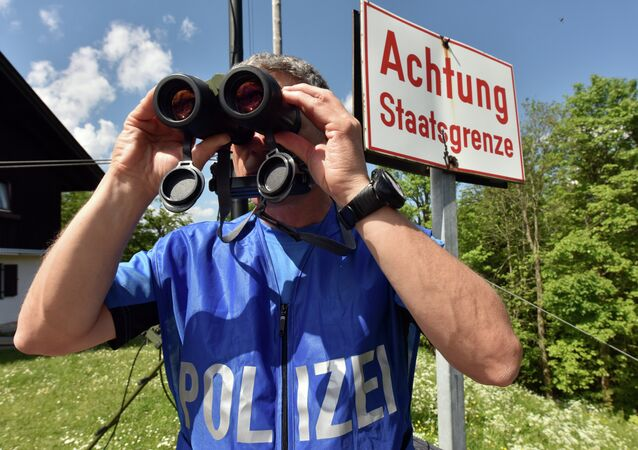 A policeman uses binoculars to secure the area on the Ederkanzel viewing platform near Mittenwald at the German-Austrian border on June 3, 2015