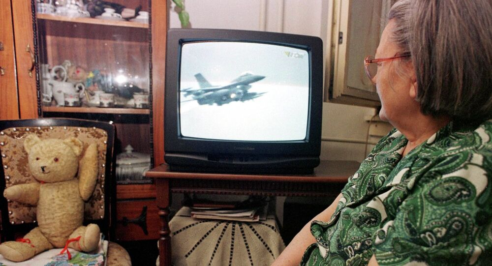An unidentified Bosnian woman watches NATO air strikes against Yugoslav military targets on a TV screen in Tuzla, Bosnia, on Wednesday night, March 25, 1999.